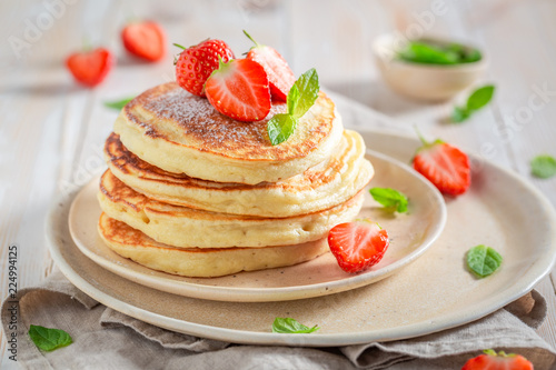 Yummy american pancakes with fresh strawberries and sugar
