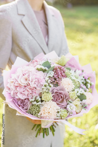 Fotobehang Hydrangea Young girl holding a beautiful spring bouquet. flower arrangement with hydrangea and garden roses. Color light pink. Bright dawn or sunset sun