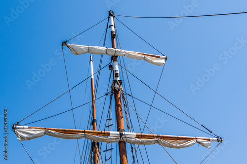 Mast of an old sea ship. Pirate wooden ship. Ropes