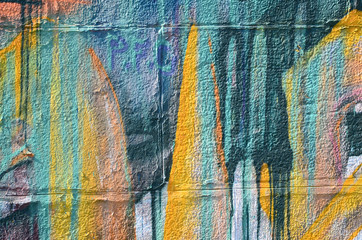 Fragment of graffiti drawings. The old wall decorated with paint stains in the style of street art culture. Colored background texture in warm tones