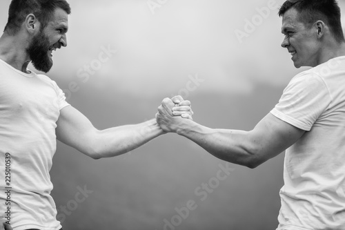 Fotografía  Strong male bodybuilders in white t-shirts greeting each other in wrestling manner outdoor over foggy mountain landscape