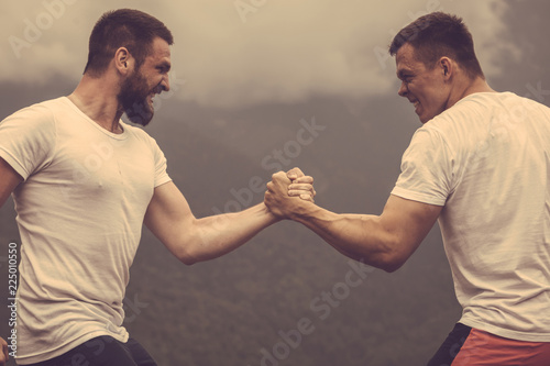 Photo  Strong male bodybuilders in white t-shirts greeting each other in wrestling manner outdoor over foggy mountain landscape