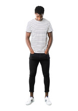 Full Body Of Dark Skinned Man With Striped Shirt Standing And Looking Down On White Background