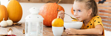 Child Eating Pumpkin Soup In Halloween Decorated Dinning Room. Autumn Season Food Lifestyle Banner.