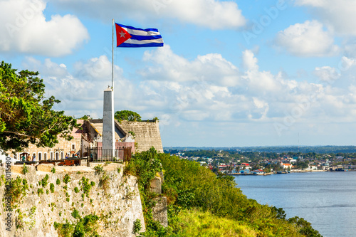 Poster de jardin Fortification La Cabana Spanish fortress walls and Cuban flag in the foreground, with sea in the background, Havana, Cuba