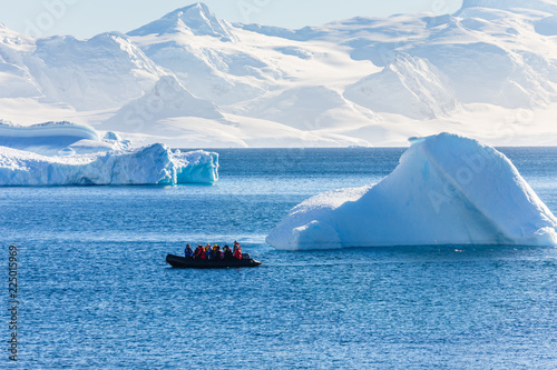 La pose en embrasure Antarctique Boat full of tourists passing by the huge icebergs in the bay near Cuverville island, Antarctic peninsula