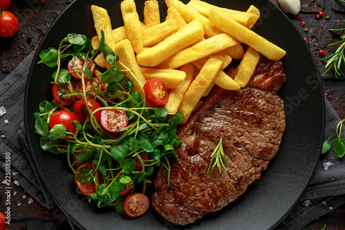 Grilled sirloin steak with potato fries and vegetables, tomato salad in a black plate. rustic table