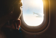 Woman Looking Out Through Airplane Window