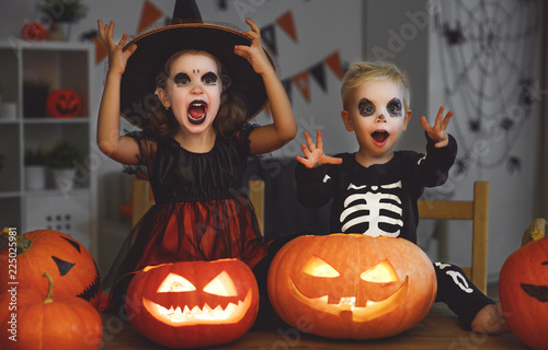 Foto  happy Halloween! children in costume of witch and skeletons with pumpkins and ca