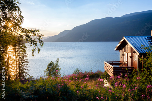 Wooden house with terrace overlooking scenic lake at sunset in Norway Scandinavi Wallpaper Mural