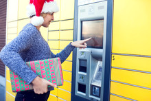 Woman With Santa Hat Client Using Automated Self Service Post Terminal Machine Or Locker To Deposit The Parcel For Storage
