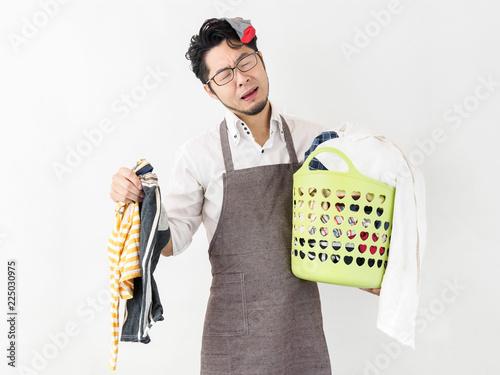 Photo 白背景の自宅にて溜まった洗濯物にまみれる日本人男性