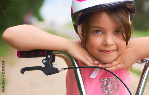 Fotografie, Obraz  Close-up of a little girl's face on bike looking at camera and smiling