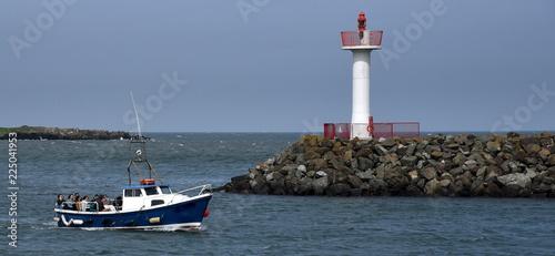Zdjęcie XXL Latarnia morska przy schronieniem Howth przed iskrzastym niebieskim niebem i łódź w przedpolu