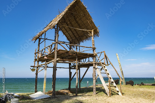 Fotobehang Tropical strand tropical sea view under wooden hut at sunny day. sandy beach and blue sky. soft cloud and island background