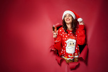 Attractive Brunette Woman In Christmas Hat And Pullover With Santa Design Coming Out Of Torn Red Background With Glass Of Champagne