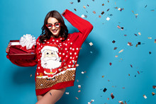 Happy Pretty Brunette Woman In Sunglasses And Red Oversize Pullover With Santa Design Standing Under Falling Confetti With Gift Box On Blue Background