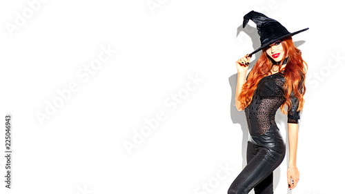 Halloween. Sexy witch with bright makeup and long red hair. Beautiful young woman posing in witches sexy costume over white background