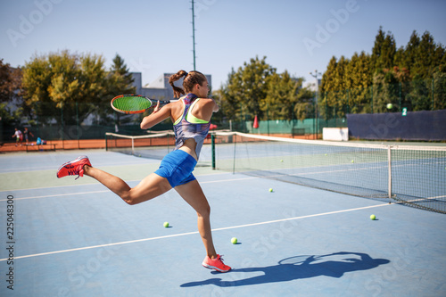Female tennis player hits the ball with Forehand drive volley.