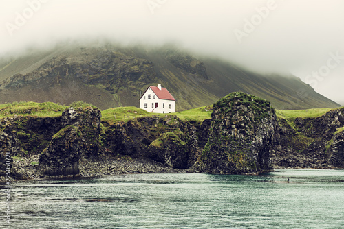 Lonely icelandic house with red roof on the sea coast with green grass meadow, rocks anf foggy sky фототапет