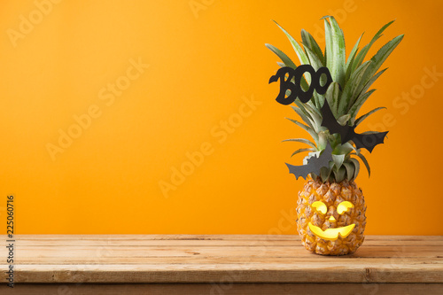 Halloween holiday concept with jack o lantern pineapple on wooden table