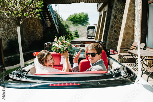 Fotografia  Happy bride and groom, newlywed wedding couple is driving a convertible retro car with balloons on a country road for honeymoon after the ceremony