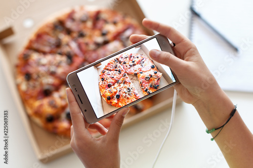 Young girl hands taking a picture of her meal - a box of pizza