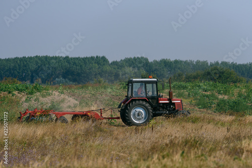 The red tractor works in the field in autumn