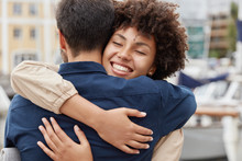 Farewell Concept. Delighted Happy Smiling African American Woman Says Goodbye To Boyfriend Who Sails For Long Time, Gives Warm Hug, Pose Together Against Harbour Background. Truthful Feelings