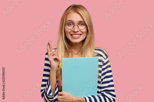 Hopeful pretty blonde student keeps fingers crossed, believes in