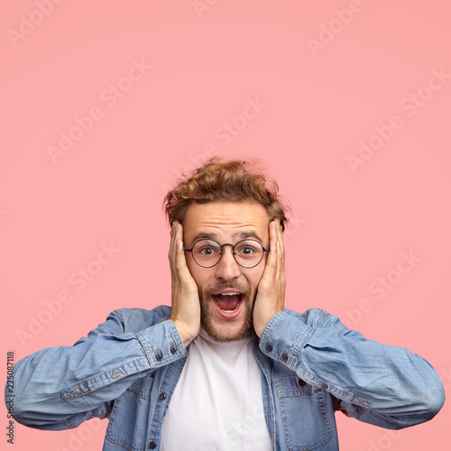 Obraz Amazed happy guy with overjoyed expression, keeps hands on face, gazes at camera with unexpected cheerful look, has curly hair, dressed in fashionable clothes, poses over pink background, free space - fototapety do salonu