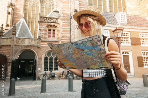 Fototapeta premium Dziewczyna podróżnik trzymać i przeglądać mapę w Amsterdamie. Hipster turysta poszukujący właściwego kierunku na mapie, przygoda z koncepcją stylu życia