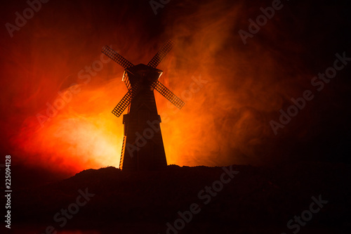Windmill silhouette standing on hill against the night sky. Night decor with old windmill on hill with horror toned foggy background with light.