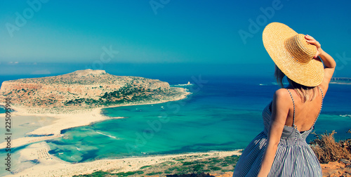 Foto  Young redhead girl in hat and dress with sea coastline on Balos, Crete, Greece