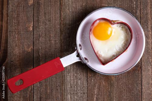 Egg in heart shape on fry pan