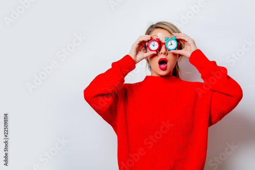 Portrait of a beautiful white woman in red sweater with little alarm clocks on white background, isolated Canvas Print