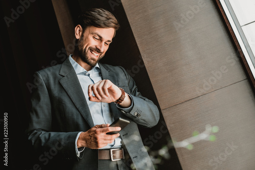 Low angle of smiling businessman wearing suit and standing indoor. He is holding mobile phone and checking time on wrist