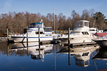 Boats Docked At A Public Pier With Water Reflections