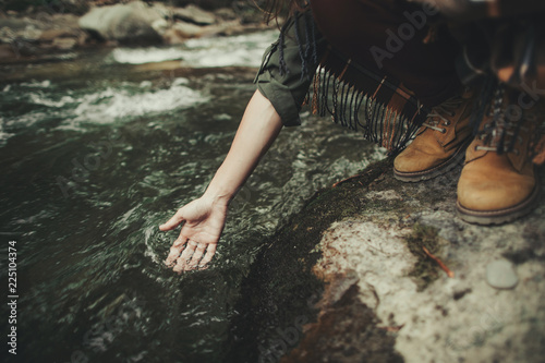 Close up of a pleasant young woman standing on the stone while holding her hand in the river