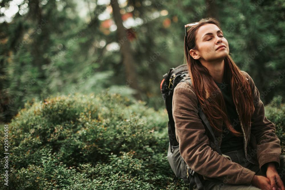 Fototapeta I feel healing energy. Portrait of serene girl with closed eyes enjoying atmosphere of coniferous wood