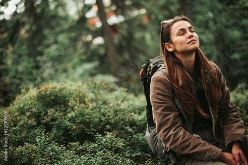 Fototapeta premium Czuję uzdrawiającą energię. Portret pogodna dziewczyna z zamkniętymi oczami cieszy się atmosferę iglasty drewno