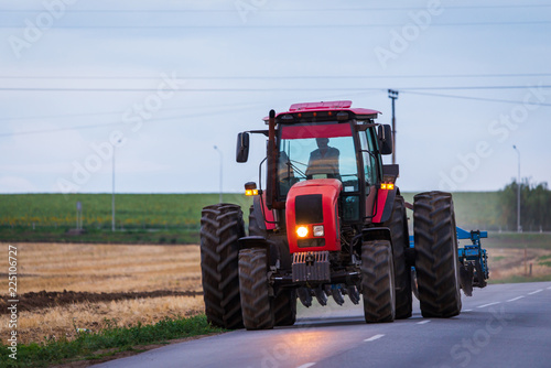 Agricultural tractor moving on the asphalt road after working in field