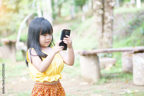 1dcbbea8890 Asian child cute or kid girl smile wear traditional top or sleeveless shirt  and playing smartphone ...