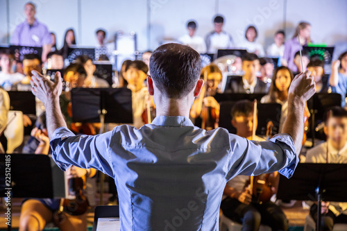 Foto Male school conductor conductiong his student band to perform music in a school