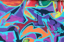 Fragment Of Graffiti Drawings. The Old Wall Decorated With Paint Stains In The Style Of Street Art Culture. Multicolored Background Texture