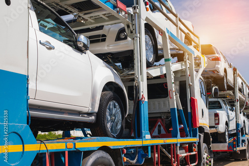 Photo  Logistics, transportation of new cars on a two-level semi-trailer truck on a two-lane paved country road in the sunny day, side view,logistic and transport concept