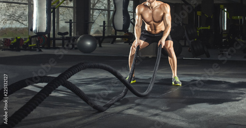 Fotografía  Athletic adult man with battle rope doing exercise in the fitness gym
