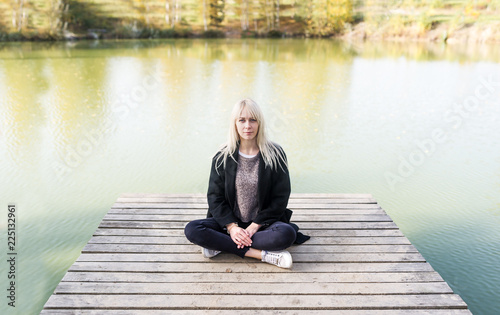Blonde young woman in black coat sitting in a lotus pose on the wooden pier