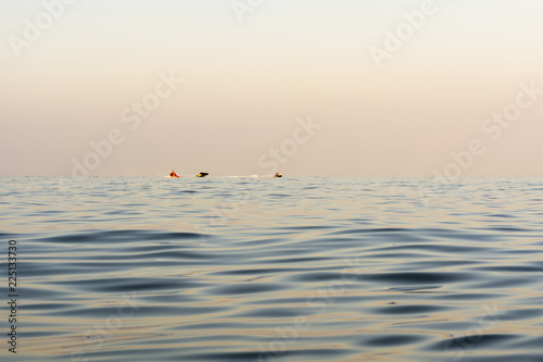 Photo  evening sea with waves, far away on a horizon line floating water bike, nature a