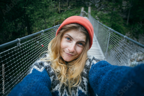 Fotografía  Cute and pretty, young girl or woman, adventurer or travel blogger, makes selfie on camera